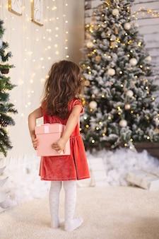 Маленькая девочка прячет рождественский подарок за спиной