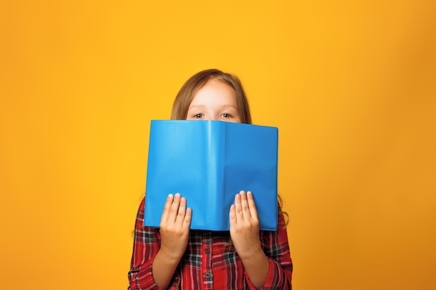A little girl is hiding behind an open book