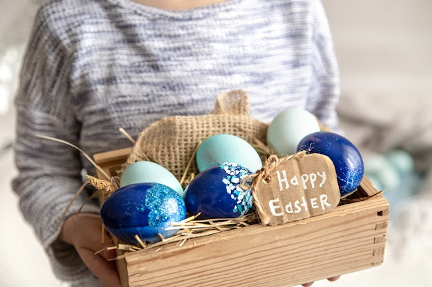A little girl is holding a basket of easter eggs. close up.