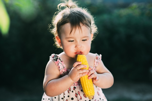 A little girl is holding boiled corn and thinking whether to eat or not