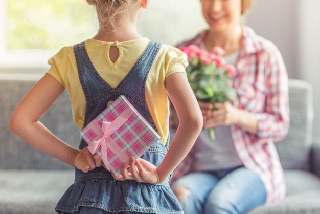 Little girl is holding a gift box for her beautiful mom.