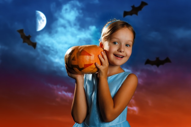 Little girl is holding a pumpkin against the background of the evening moon sky.