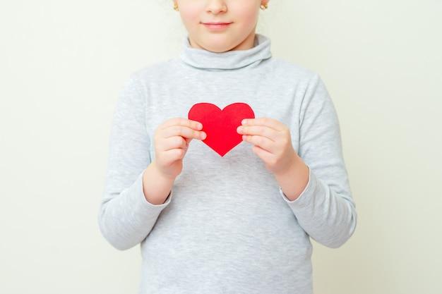 Little girl is holding red little heart.