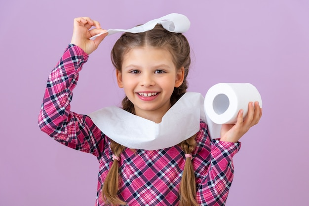 A little girl is holding toilet paper in her hand and smiling on purple background