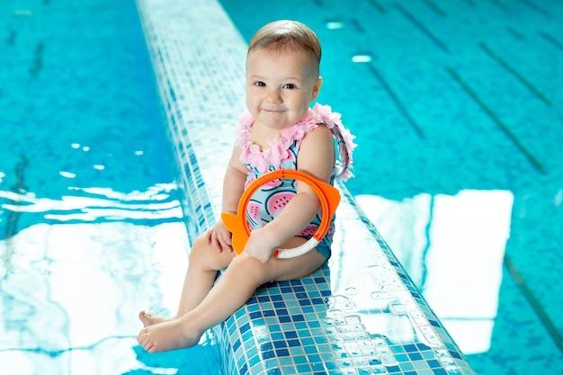 Маленькая девочка смеется в бассейне на уроке плавания.