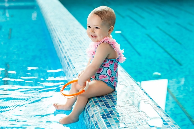 Little girl is laughing in the pool at a swimming lesson.
