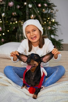 Little girl is laughing with her friend, dachshund dog