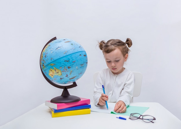 Little girl is learning with a notebook and pen on a white isolated
