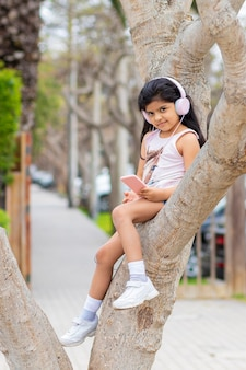 어린 소녀는 나무에 그녀의 헤드폰으로 음악을 듣고
