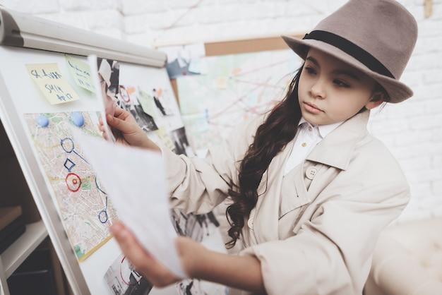 Маленькая девочка смотрит на фотографии возле доски улик.