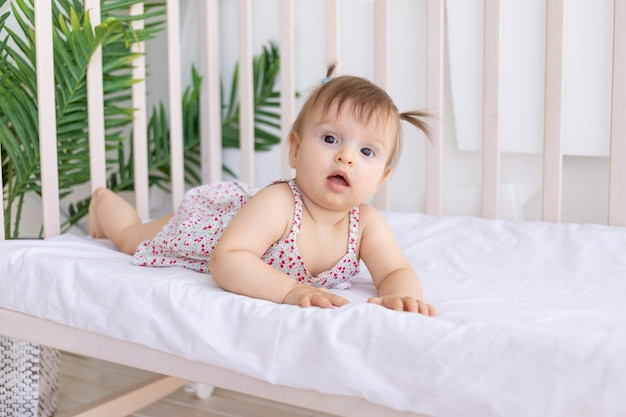 A little girl is lying in a crib in a bright room