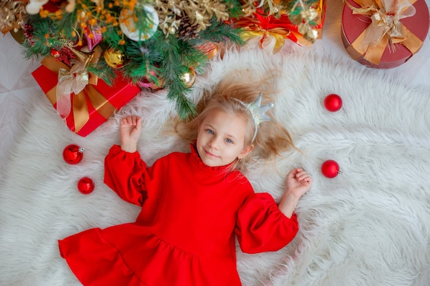 A little girl is lying near the christmas tree at home top view