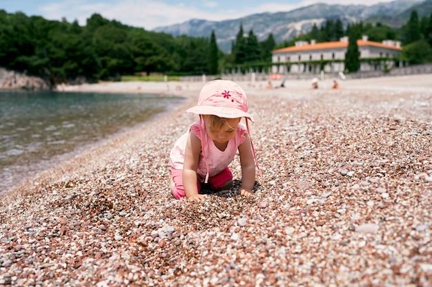 小さな女の子は、ミロサーヴィラを背景に水辺のビーチで四つんばいになっています