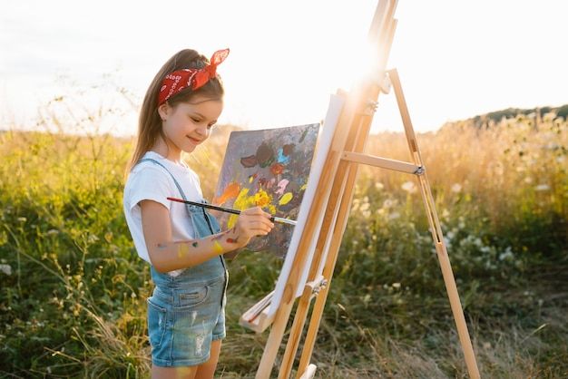 Little girl is painting picture outdoors
