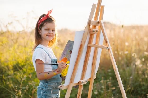 Маленькая девочка рисует картину на открытом воздухе