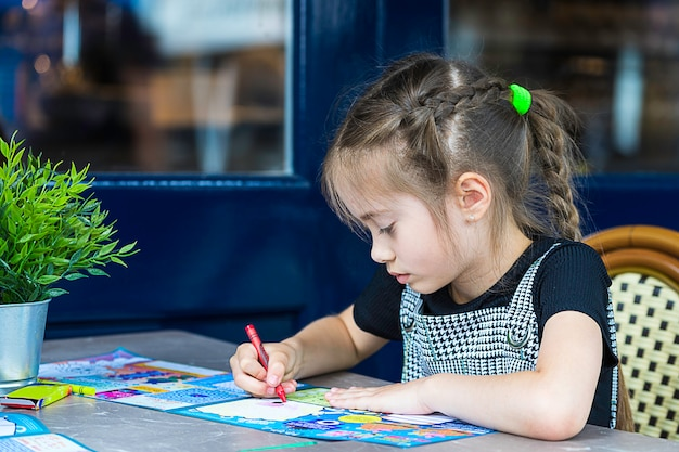 Little girl is painting with crayons