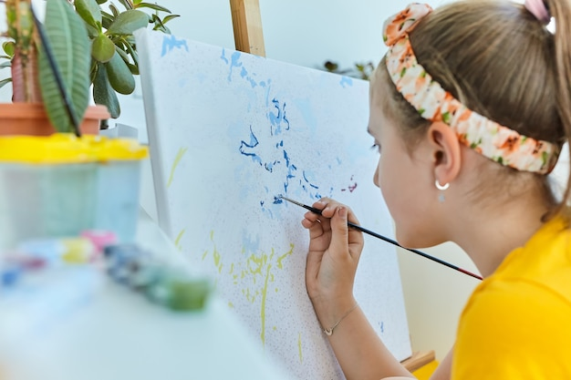 Маленькая девочка рисует гуашью. счастливая картина маленькой девочки дома. девушка рисует картинку по номерам. крупным планом, выборочный фокус.