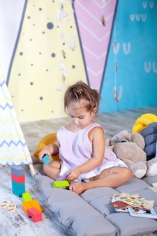 Little girl is playing on floor with colorful cubes. baby plays with toys in children's room. little girl plays in kindergarten. childhood concept, child development. happy child playing with blocks.