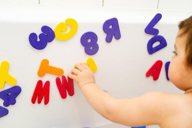 Маленькая девочка играет пены lettern в ванне. изучение азбуки с игрой. монтессори-деятельность