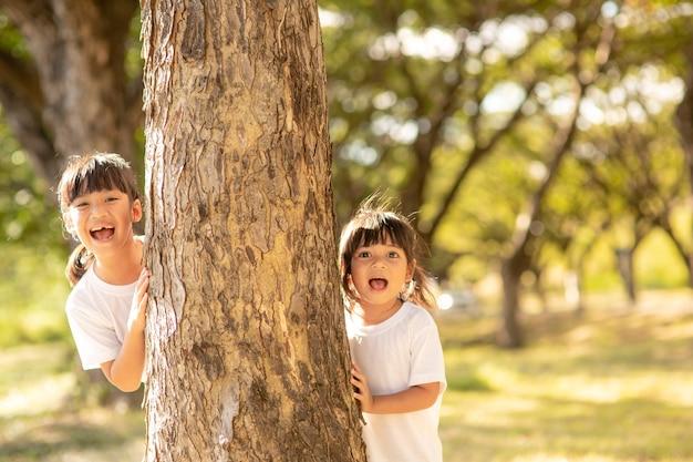 어린 소녀가 공원에서 숨바꼭질을 하고 있다