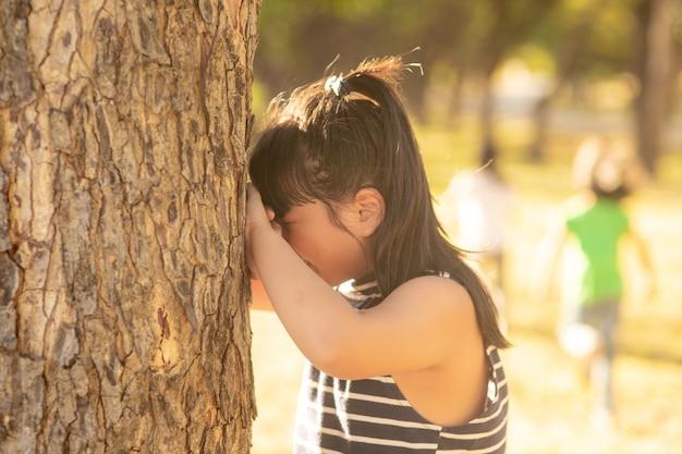 어린 소녀가 공원에서 숨바꼭질을 하고 있다 프리미엄 사진