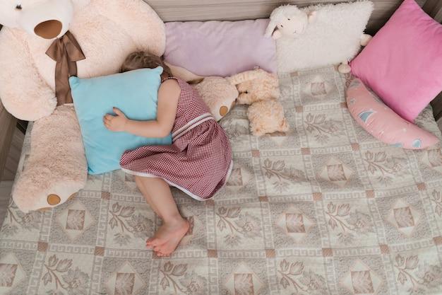 Маленькая девочка играет в прятки в своей комнате