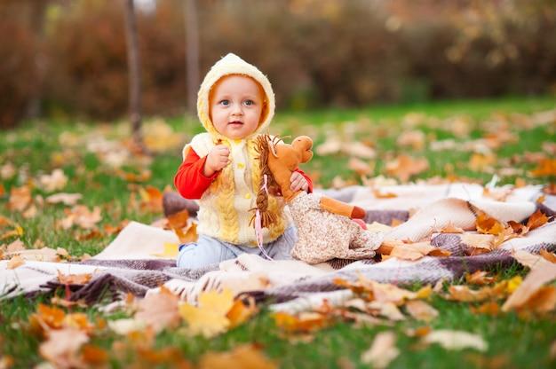 Маленькая девочка играет в осенний парк с улыбкой.