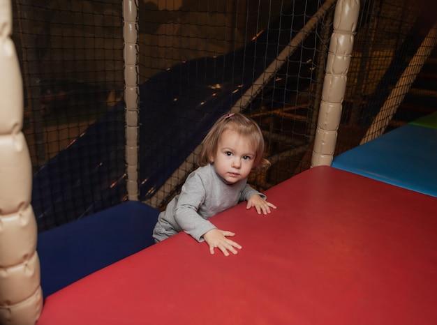Маленькая девочка играет в детском развлекательном центре