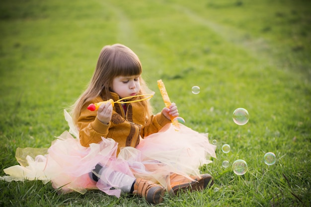 Little girl is playing with bubbles outdoor