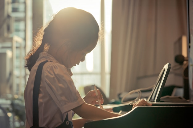 Little girl is playing with piano and music tablet at home