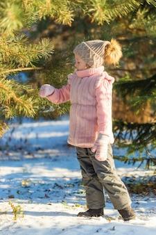 어린 소녀는 겨울 숲에서 소나무와 놀고있다. 행복한 어린 시절. kids outdoors. 겨울 재미있는 휴가 개념