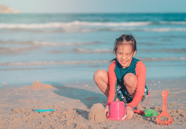Little girl is playing with plastic toy and sand on the beach