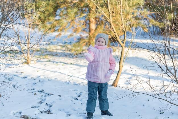 어린 소녀는 겨울 숲에서 눈으로 재생됩니다. 행복한 어린 시절. 겨울 재미 휴가 개념