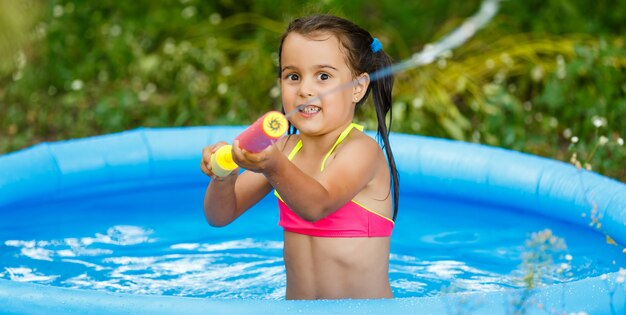 Little girl is playing with a water pump in an inflatable pool in a garden