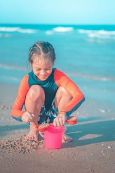 Little girl is playing with wave and sand on the beach