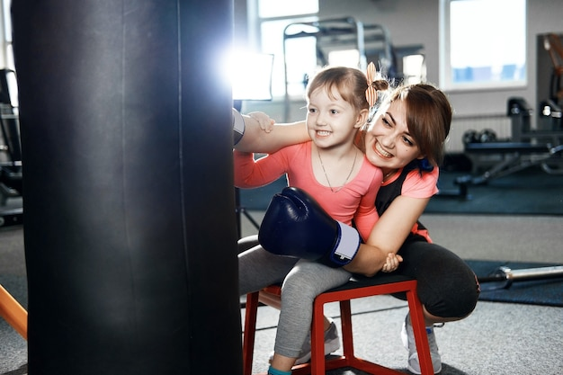 Little girl is practicing boxing, girl teaches mom to box, funny mother and daughter in the gym