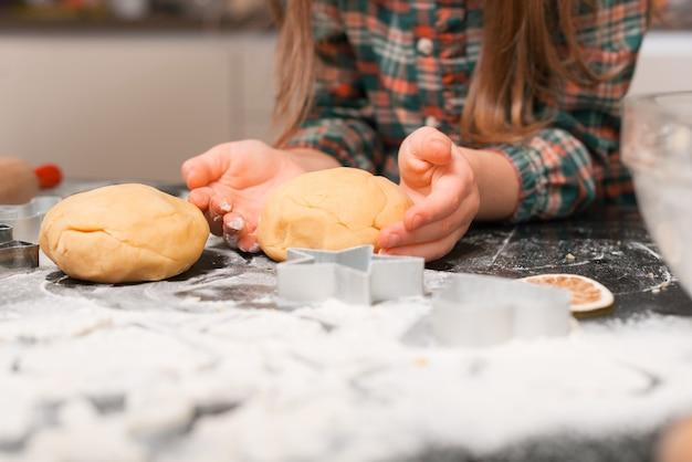 Маленькая девочка готовит тесто для пряников.