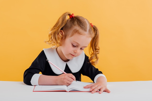 Little girl is preparing for school, writes in the notebook, dressed in school uniform sitting at the white table