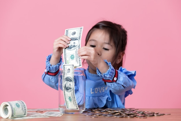 Little girl is putting the banknote in a clear glass jar