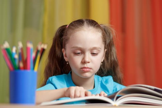 少女はテーブルに座って本を読んでいます