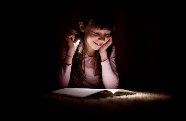 Little girl is reading a book with a flashlight in a dark room at night.