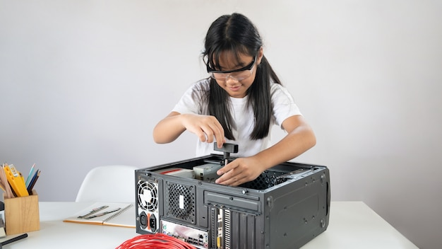 A little girl is repairing computer hardware at the white working table.