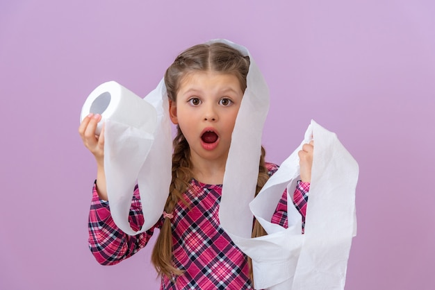 A little girl is shocked by a roll of toilet paper.