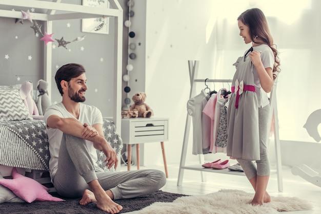 Маленькая девочка показывает папе красивое праздничное платье.