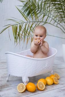어린 소녀는 아기 목욕에 앉아서 텍스트를 위한 장소가 있는 흰색 배경에 레몬을 먹고 있습니다. 어린이를 위한 수처리