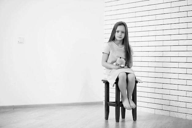 어린 소녀가 의자에 앉아 카메라에 포즈를 취하고 있다