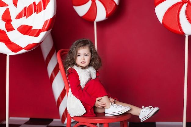 小さな女の子は赤い背景の上の大きなクリスマスキャンディーと椅子に座っています