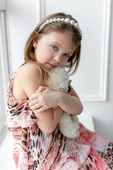 A little girl is sitting at the window with a toy in her arms