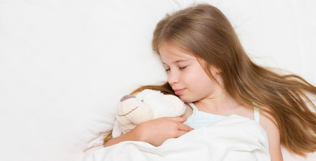 A little girl is sleeping in a stuffed polar bear toy. there is long hair on the pillow.