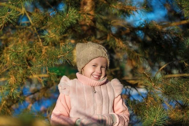 어린 소녀는 겨울 숲에서 웃. 행복한 어린 시절. kids outdoors. 겨울 재미있는 휴가 개념